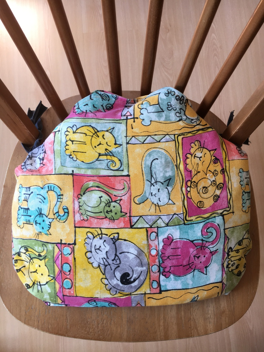 Seat cushion on wooden chair. The cushion is made from fabric covered in cartoon images of cats.